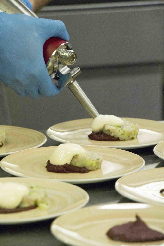 Koch im 'August und Maria' trägt Sauce Hollandaise auf Bachforelle auf.